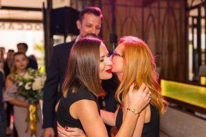 dwie kobiety całują się w policzek