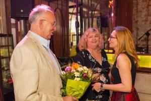 dwie kobiety i mężczyzna z kwiatami